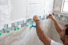 stock-photo-80422033-tile-series-tile-border-being-installed-on-shower-wall-in-home